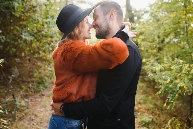 Baciare la giovane coppia innamorata nel parco d'autunno