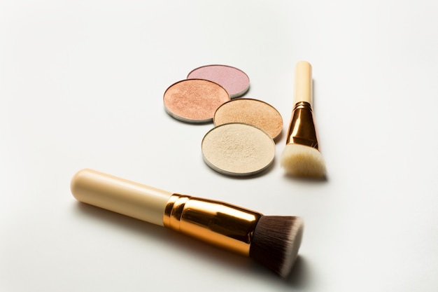 Kit di evidenziatori con pennelli cosmetici su sfondo bianco