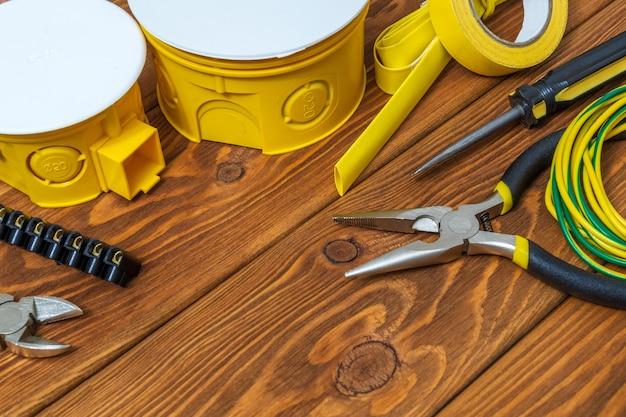 Kit ricambio giallo per impianti elettrici e attrezzi preparati su assi di legno d'epoca prima della riparazione o messa a punto