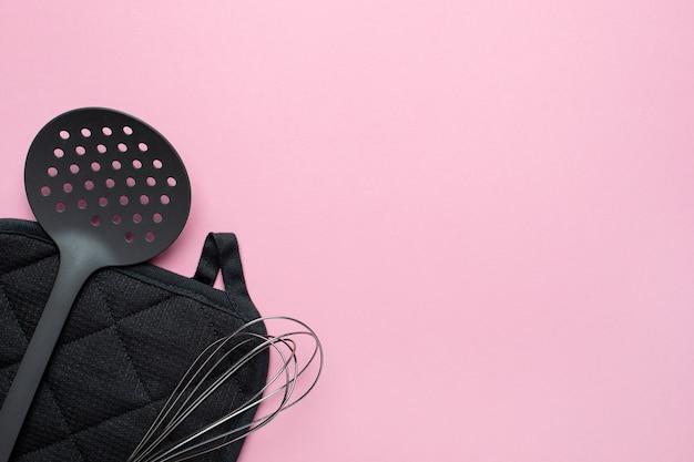 Accessori da cucina spatola frusta su sfondo rosa