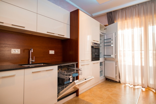 La cucina dell'appartamento. il design della cucina. cucina in legno, frigorifero, piano cottura, tavolo da pranzo. cucina interna.