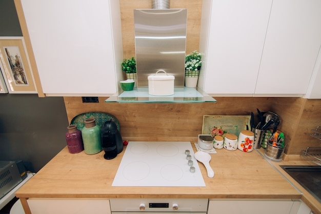 La cucina dell'appartamento. il design della cucina. cucina in legno, frigorifero, piano cottura, tavolo da pranzo. interno della cucina