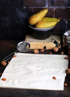 Sfondo cucina cottura in stile retrò muro di mattoni grunge pera mandorla filo pasta mattarello setaccio
