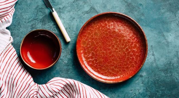 Piatto di ceramica rosso del fondo della cucina su un fondo blu