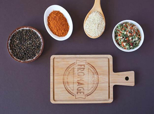 Tagliere da cucina, pepe nero, pepe rosso, semi di sesamo ed erbe essiccate