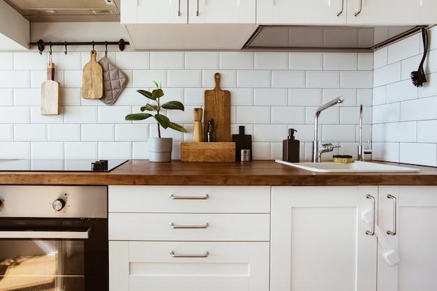 Utensili da cucina in ottone accessori da chef cucina pensile con parete in piastrelle bianche e piano in legno verde...