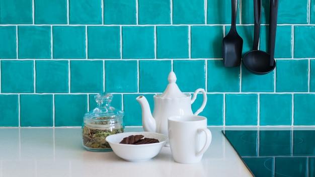 La cucina presenta mobili frontali piatti grigio scuro abbinati a piani in quarzo bianco e una piastrella blu lucida.