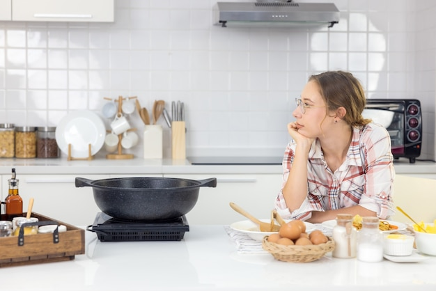 Nella cucina di casa, una bella donna con una tavoletta prepara un pasto a base di pasta e un'adorabile giovane donna mangia la pasta.