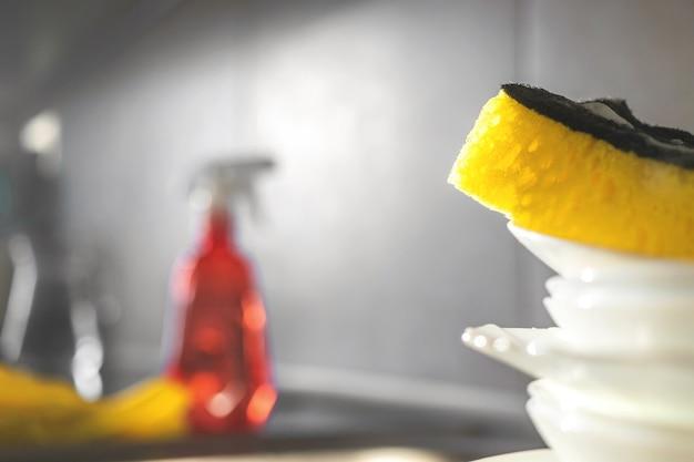 Sfondo di lavori domestici in cucina con posto per il testo, piatti non lavati con spugna gialla, foto di messa a fuoco selettiva