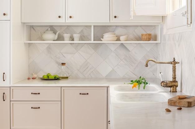 Interno della cucina con luce naturale e mobili in stile rustico con pareti in marmo piastrellato