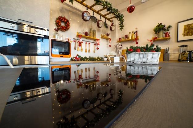 Un'isola cucina con piano cottura che riflette la decorazione natalizia della cucina per la festa di natale in famiglia....