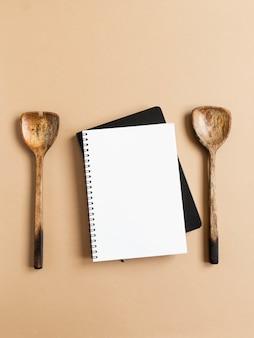 Blocco note da cucina e ricettario nero mock up per testo culinario e cucchiai di legno