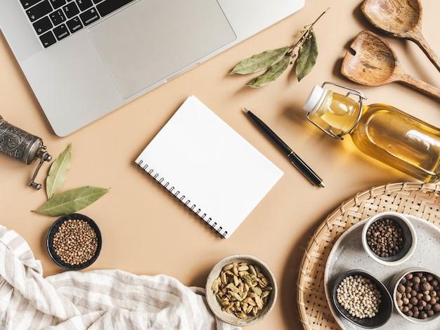 Mockup di blocco note da cucina per testo culinario, laptop, olio in bottiglia e spezie