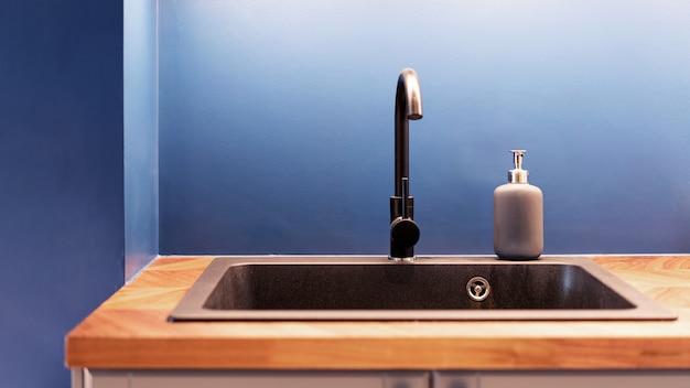 Lavello e rubinetto della cucina. lavello da cucina verniciato cromato adatto al piano di lavoro in legno con acqua di rubinetto e bottiglia per pompa per sapone liquido.