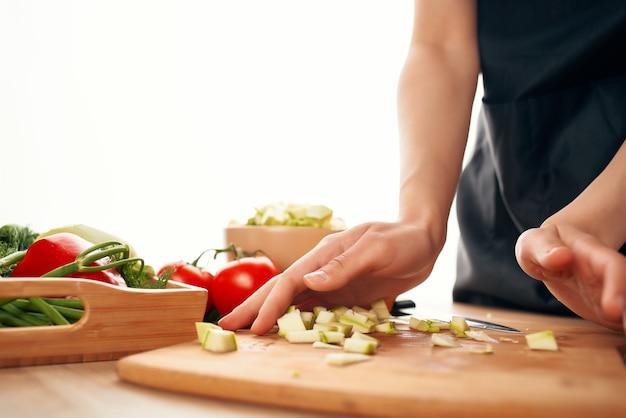 Cucina per affettare le verdure che cucinano i primi piani degli ingredienti