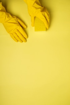 Spugne della cucina e guanti di gomma su fondo giallo