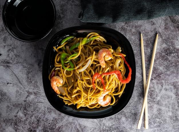 Cucina mescolare le tagliatelle udon, verdura, gamberetti, con le bacchette di legno su uno spazio grigio strutturato. pavimento piatto. cena in stile asiatico
