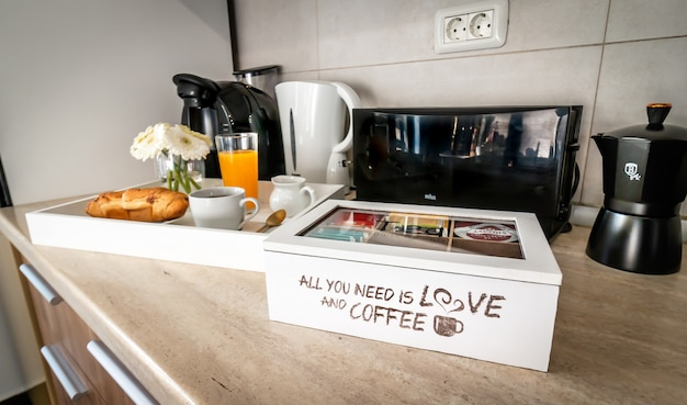 Tavolo della cucina. elettrodomestici. mattina, caffè, caffè espresso, succo d'arancia, cornetto, fiore
