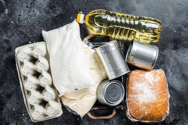 Tavolo da cucina con prodotti alimentari di donazione, concetto di aiuto in quarantena. olio, conserve, pasta, pane, zucchero, uova. tavolo nero. vista dall'alto.