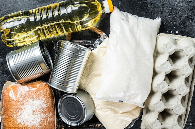 Tavolo da cucina con beni alimentari di donazione, concetto di aiuto in quarantena. olio, conserve, pasta, pane, zucchero, uova.