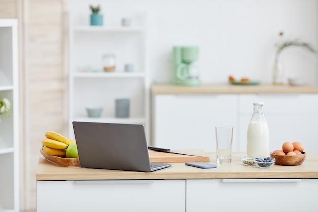 Tavolo da cucina con frutta e computer portatile su di esso nella cucina domestica