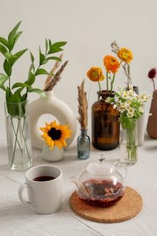Tavolo da cucina con tazza bianca in porcellana, teiera con tè nero, gruppo di fiori vari e fiori di campo essiccati in vasi in piedi sulla parete