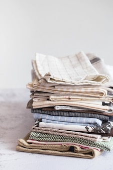 Tessile da cucina. pila di tessuti in diversi colori e trame, primo piano. asciugamani da cucina