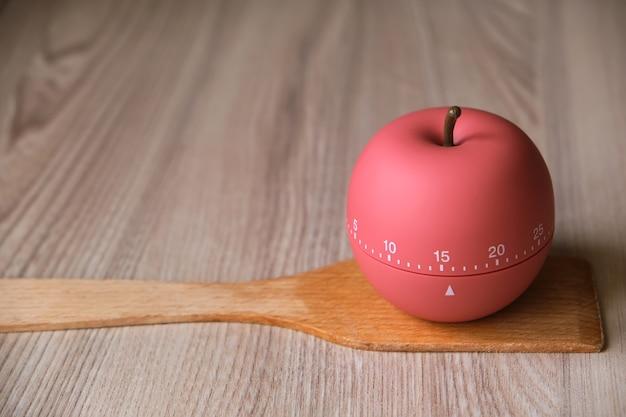 Il timer da cucina a forma di mela si erge su una spatola di legno per cucinare o cuocere in cucina