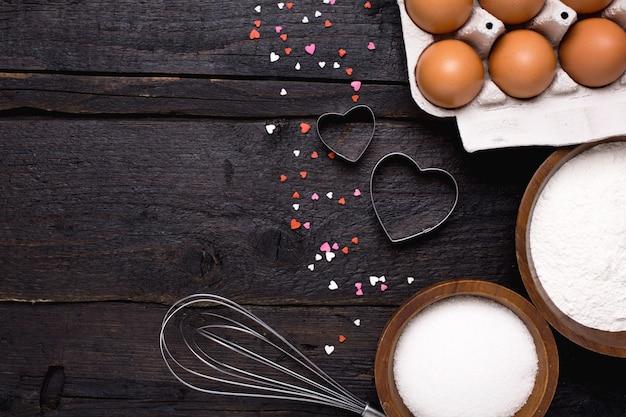 Utensili da cucina, farina, cuori e zucchero su legno