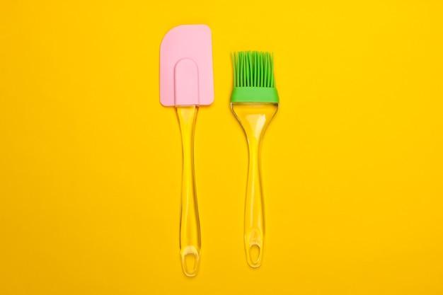 Utensili da cucina. spatola da cucina e pennello su un giallo. minimalismo.