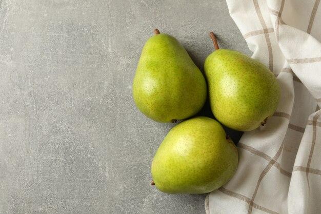 Asciugamano da cucina e pere verdi sul tavolo grigio