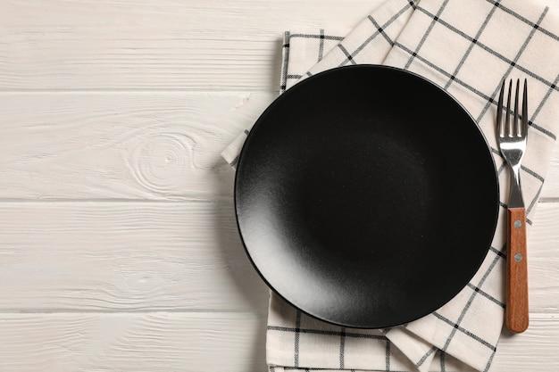 Asciugamano di cucina con la coltelleria su fondo di legno, vista superiore