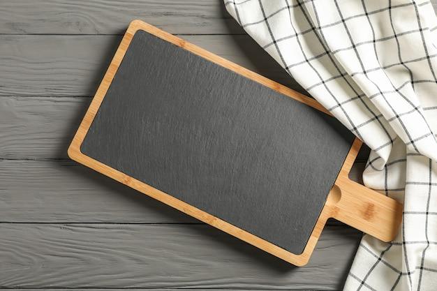 Asciugamano di cucina con il tagliere su fondo di legno, vista superiore