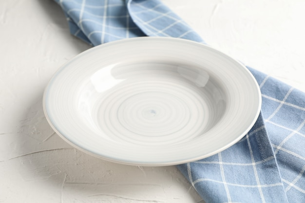 Asciugamano di cucina con il piatto su fondo bianco, primo piano