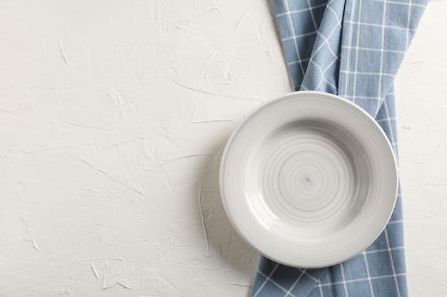Asciugamano di cucina con il piatto su fondo bianco, vista superiore
