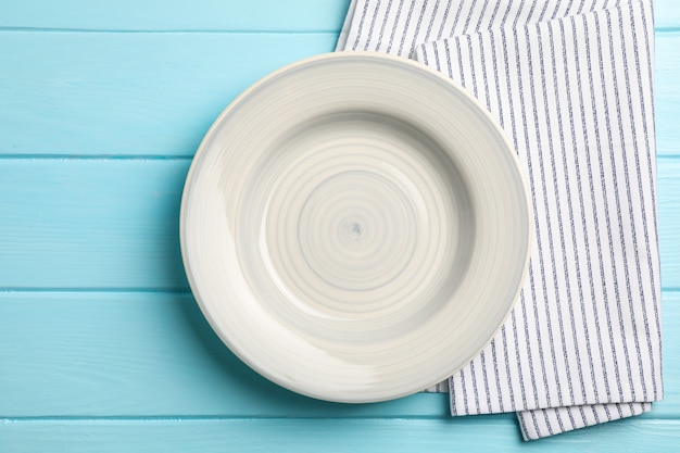 Asciugamano di cucina con il piatto su fondo di legno, vista superiore