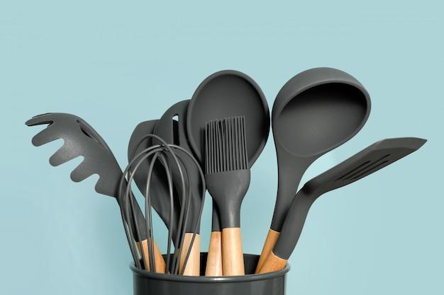 Fondo degli utensili della cucina con copyspace, concetto domestico della decorazione della cucina, strumenti della cucina, accessori di gomma in contenitore. Foto Premium