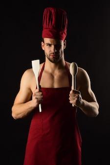 Concetto di utensili da cucina uomo barbuto serio con cappello da cuoco e grembiule con spatola da cucina in legno e