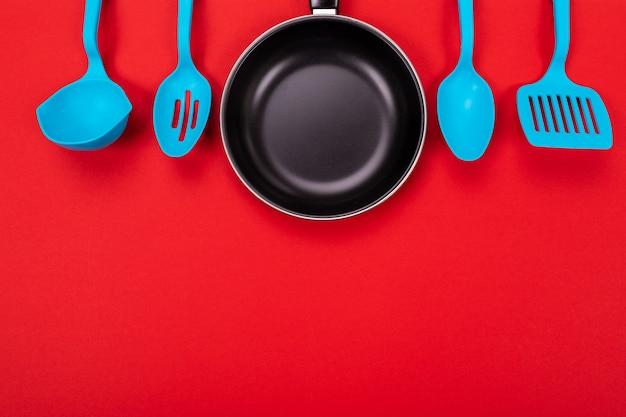 Utensili della cucina per la cottura nella cucina isolata con copyspace su rosso