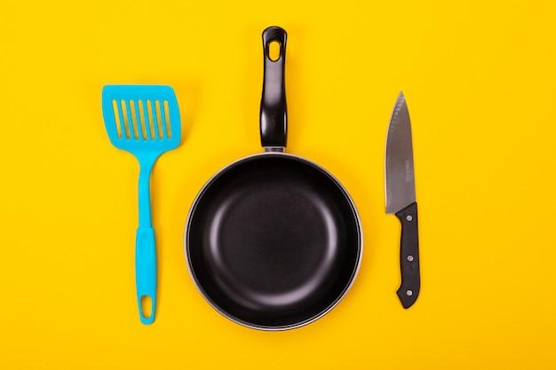 Utensili della cucina per la cottura nella cucina isolata con copyspace