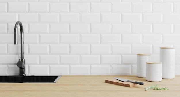 Gli aggeggi degli utensili della cucina si avvicinano al lavandino nero su superficie di legno e sulla parete piastrellata bianca