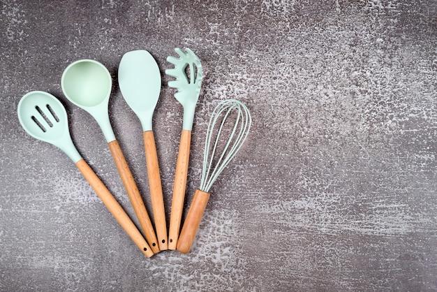Utensili da cucina, utensili da cucina domestica, accessori in gomma menta su sfondo scuro. ristorante, cucina, cucina, tema cucina. spatole e pennelli in silicone, spazio libero per il testo.