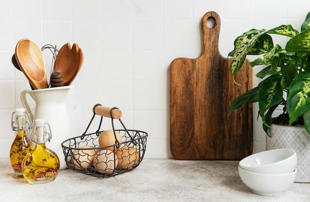 Utensili da cucina, utensili e stoviglie sulla parete di piastrelle bianche di superficie