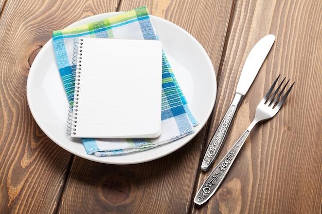 Utensili da cucina su sfondo tavolo in legno con blocco note per spazio copia