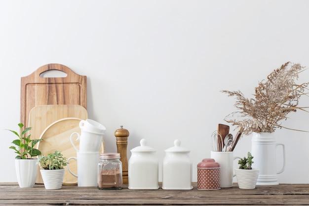 Utensili da cucina sulla tavola di legno in cucina bianca