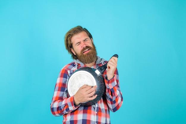 Stoviglie da cucina navi da cucina pubblicità della cucina uomo barbuto gioca con la padella come la chitarra chef pazzo
