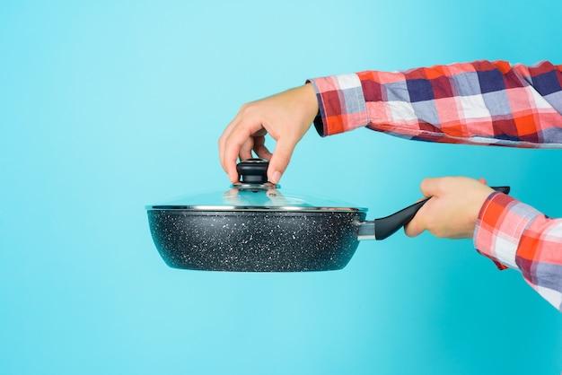 Stoviglie. vasi da cucina. pubblicità in cucina. uomo barbuto con padella. cuoco unico dell'uomo con la padella. cucinando. utensili da cucina.