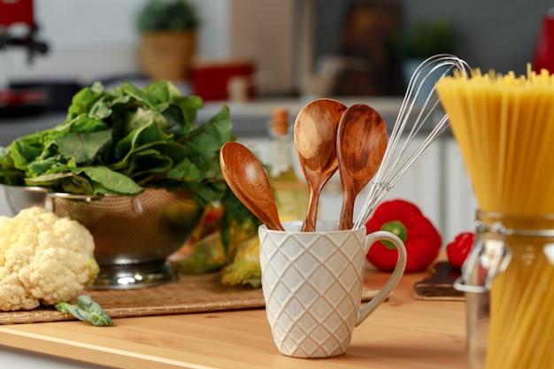 Utensili da cucina in una tazza sul tavolo della cucina