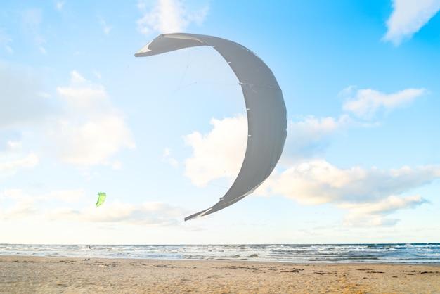 Kiteboarder prepara il suo kite per iniziare sulla spiaggia del mare