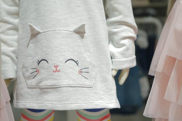 Fumetto del gattino sul maglione grigio chiaro del bambino.